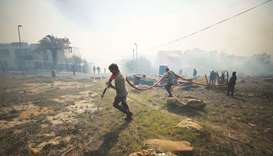 Residents and voluntary firefighters battle to contain a fire fanned by strong winds on the slopes o