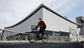 A man wearing a protective mask amid the coronavirus disease (Covid-19) outbreak cycles past Ariake