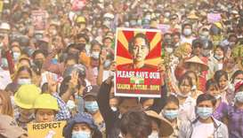 a protester holding up a poster featuring detained civilian leader Aung San Suu Kyi