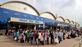 People queue to enter the Lokmanya Tilak Terminus railway station to board trains, amidst the spread