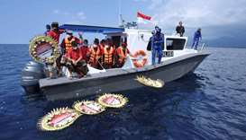 People throw flowers and petals with names of the sunken KRI Nanggala-402 submarine crew members fro