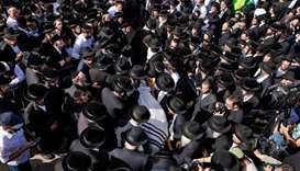 Ultra-Orthodox Jewish men take part in a funeral ceremony in Jerusalem for a victim of an overnight
