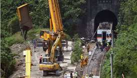A crane lifts the wreckage of a truck which was hit by the train a day after the deadly train derail