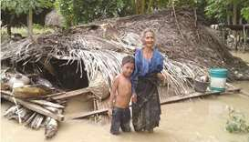 An elderly villager and her grandson stand in floodwaters in front of their damaged home in the vill