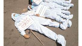 Protesters wearing protective suits and masks display placards laying on the street near the Electio