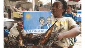 A fish vendor holds a poster with photographs of incumbent Benin President Patrice Talon (right on p