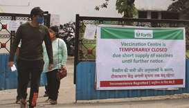 People walk past a banner announcing the temporary closure of a vaccination centre due to shortage o