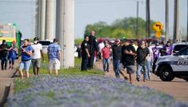 Bryan police officers direct workers away from the scene of a mass shooting at an industrial park in