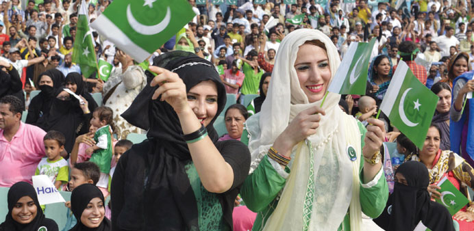 Pakistanis attend a flag hoisting ceremony to celebrate Independence Day on the Pakistan-India borde