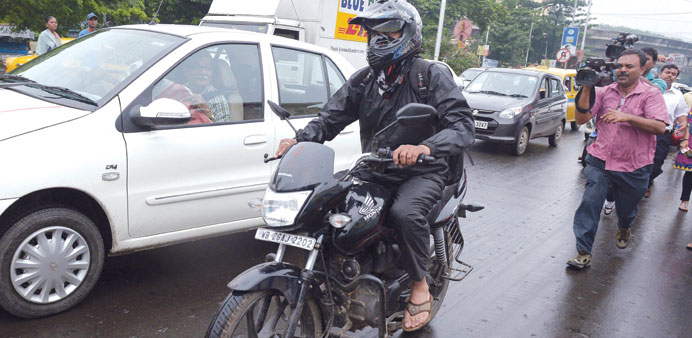 Siddharth Das tries to avoid the media as he travels on his motorcycle on a busy road in Kolkata yes