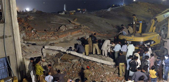 Pakistani soldiers and rescuers search the victims in the rubble of a collapsed factory on the outsk