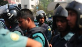 Bangladesh Police stand guard at the site of attack