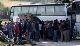 People board in a bus in order to leave the refugee makeshift camp on the Greek border