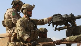 Armed men in uniform identified by Syrian Democratic forces as US special operations ride in the bac