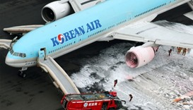 An aerial picture shows fire fighters spraying foam at the engine of a Korean Air Lines plane