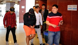National Bureau of Investigation (NBI) agents escort suspect Joshua Habalo during a press conference