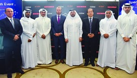 Chief executive officer Waleed al-Sayed and other Ooredoo Qatar officials flank international partne