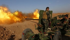Iraqi Kurdish Peshmerga fighters fire an anti-tank cannon on the front line near Hasan Sham village