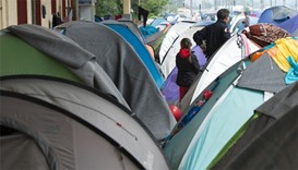 People stand next to tents for migrants