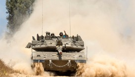 An Israeli tank rolls along the border near Gaza