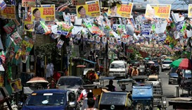 Election posters of Philippine candidates are seen hanging above vehicles driving along a main stree