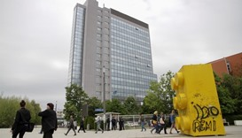 People walk in front of the parliament building in Pristina, Kosovo