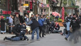Police officers detain protesters who came to celebrate May Day at Taksim Square in central Istanbul