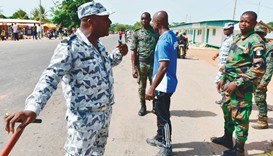 A policeman talks with soldiers as they prepare to leave a roadblock at the entrance of Bouake yeste