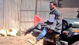 Videograb showing Farooq Ahmad Dar bound to the front of an army jeep