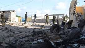Somali soldiers stand next to the attack site