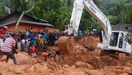 Sri Lankan military rescue workers and villagers search for survivors at the site of a mudslide