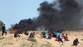 Palestinian protesters take cover during clashes