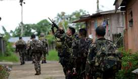 Philippine soldiers patrol a deserted neighbourhood