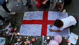 People write messages on an English national flag during a vigil for the victims of an attack on con