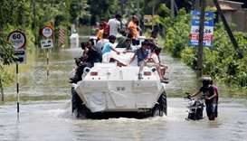 People travel on top of a armoured personnel carrier on a flooded road