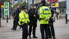 Armed police stand guard near the start of the Great Manchester Run