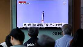 People watch a television broadcasting a news report on North Korea firing a missile