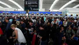 People wait with their luggage at the British Airways check in desks at Heathrow Terminal