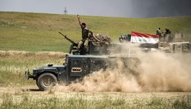 A member of the Iraqi forces' Emergency Response Division (ERD) rides on top of a humvee advancing o