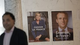 A poll worker stands next to posters for presidential candidates Marine Le Pen and Emmanuel Macron