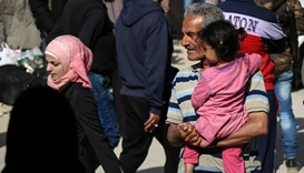 Syrian families of opposition fighters gather at a staging point in the Barzeh neighbourhood of the