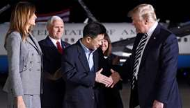 US President Donald Trump (R) shakes hands with US detainee Tony Kim (C) as US Vice President Mike P