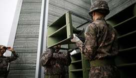 South Korean soldiers dismantle loudspeakers that were set up for propaganda broadcasts