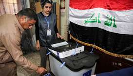 An Iraqi voter dips his finger in ink before casting his ballot at a poll station in the capital Bag