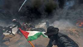 Palestinian demonstrators run for cover from Israeli fire and tear gas during a protest