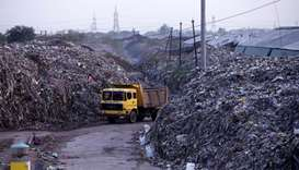 Smoke billows as a truck drives past the waste of leather tanneries at a dumpyard in Kanpur