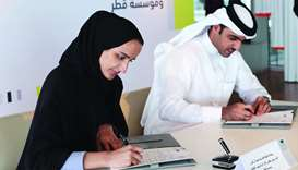 HE Sheikha Hind bint Hamad al-Thani and Khalifa al-Kuwari sign the agreement.