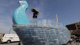 Activists build a boat from plastic water bottles at the ancient port of the Lebanese coastal city o