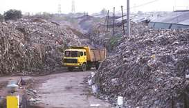 Smoke billows as a truck drives past the waste of leather tanneries at a dumpyard in Kanpur, India,