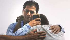 Abdul Aziz Sheikh is comforted by a relative at his Karachi home.